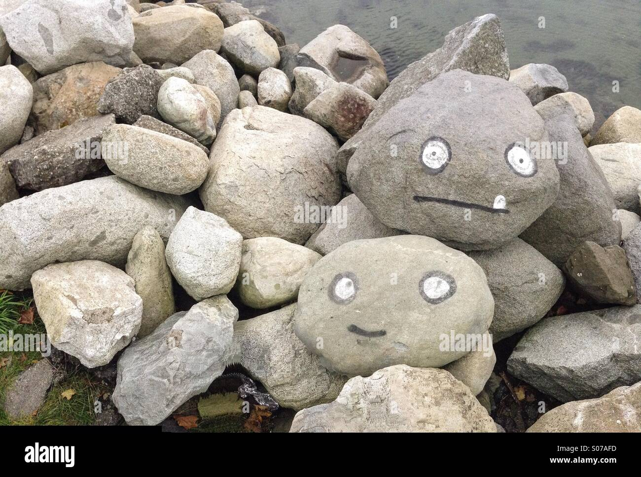 Painted faces on boulders - Stock Image