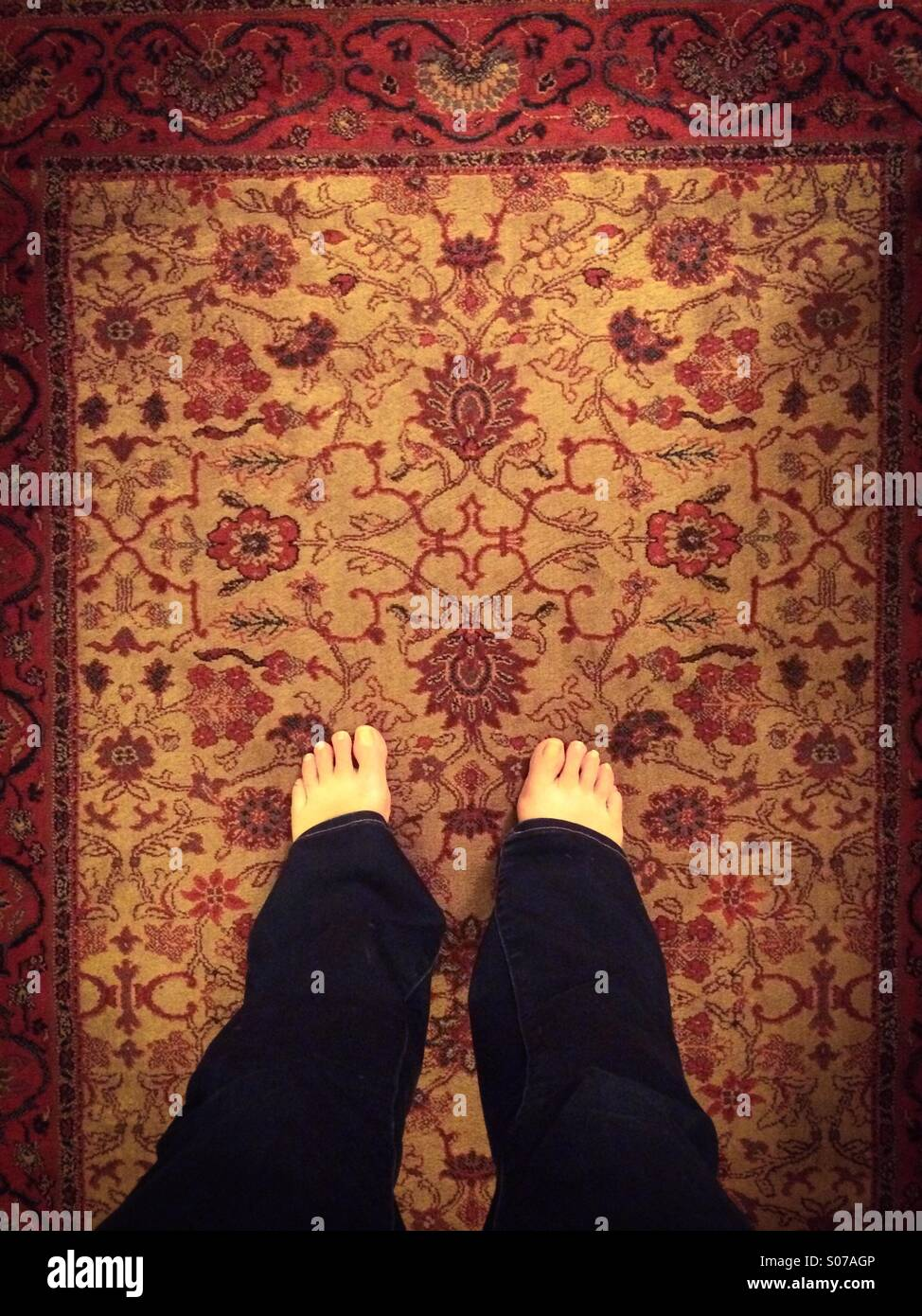 Bare feet on rug - Stock Image