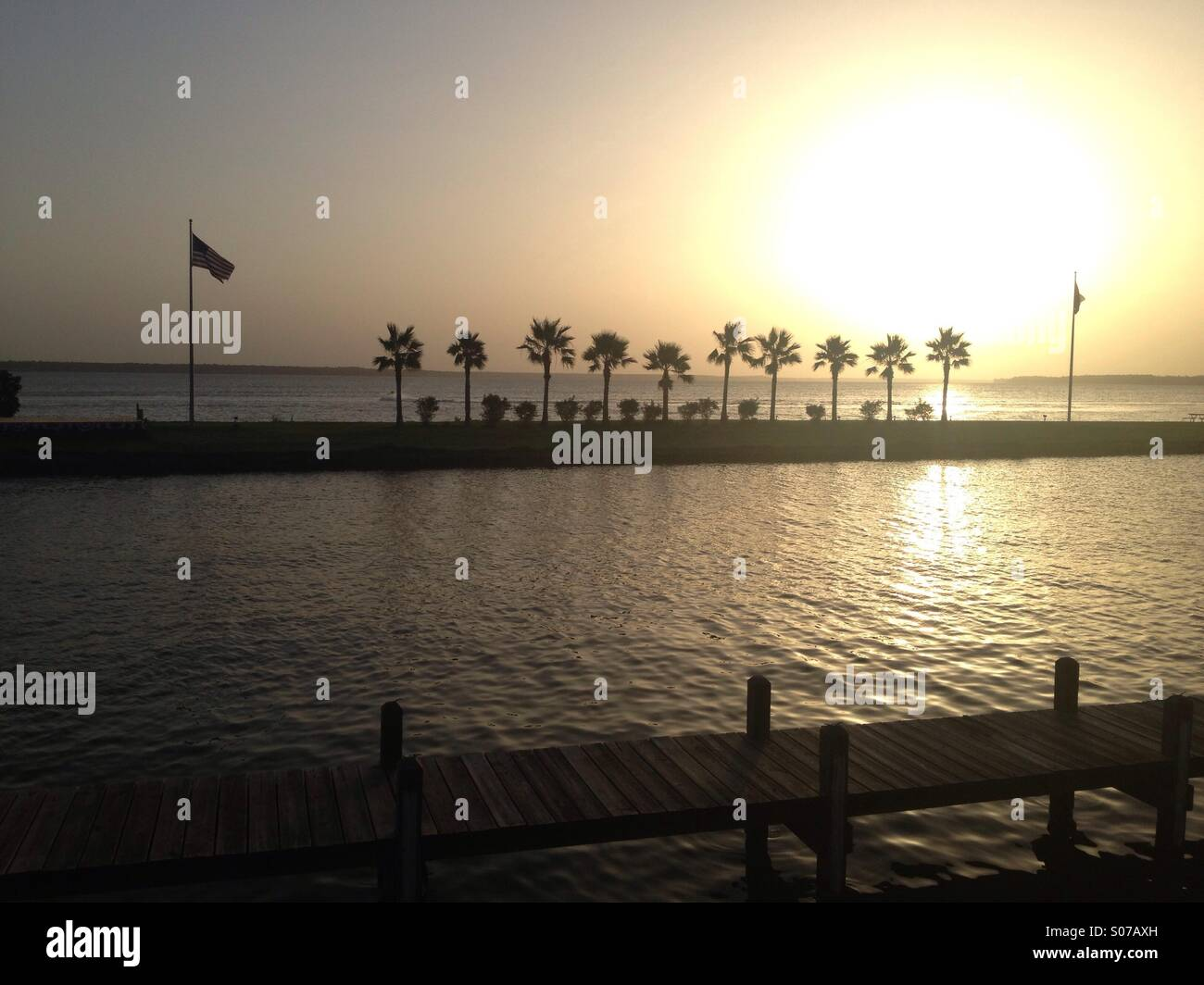 Sunset on Lake Livingston, Texas with silhouetted palm trees & flags - Stock Image