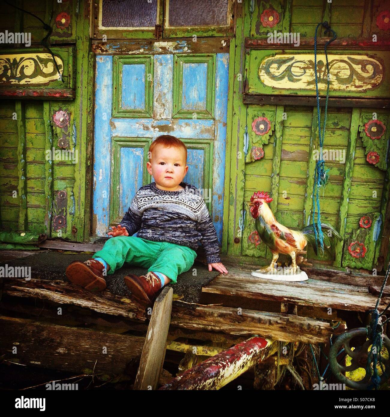 Little boy sits on bow top Gypsy Wagon Stock Photo