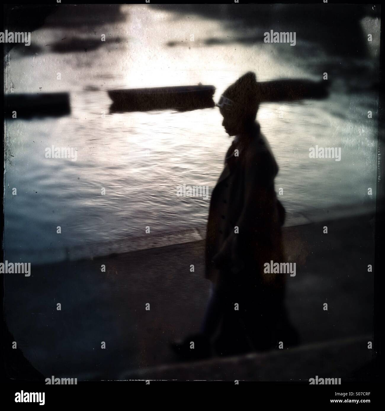 Silhouette of woman walking by the river Thames - Stock Image