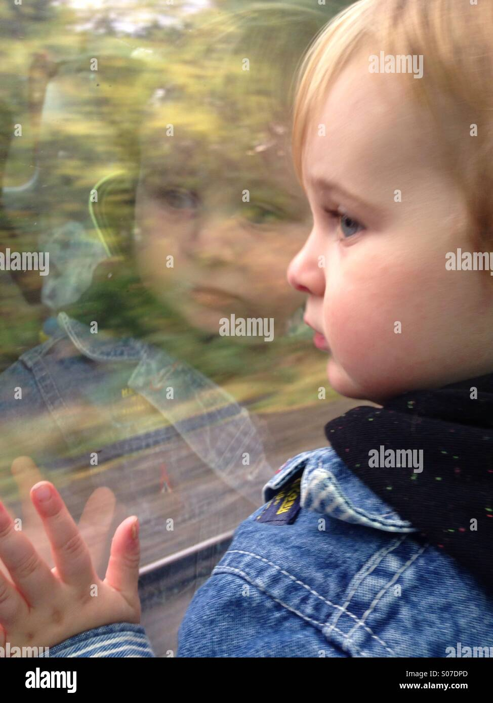 Mother amusing her toddler on a long train journey by taking selfies with her IPhone. - Stock Image