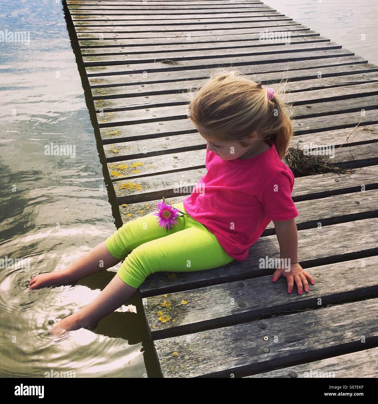 Young girl sitting at the waters edge - Stock Image