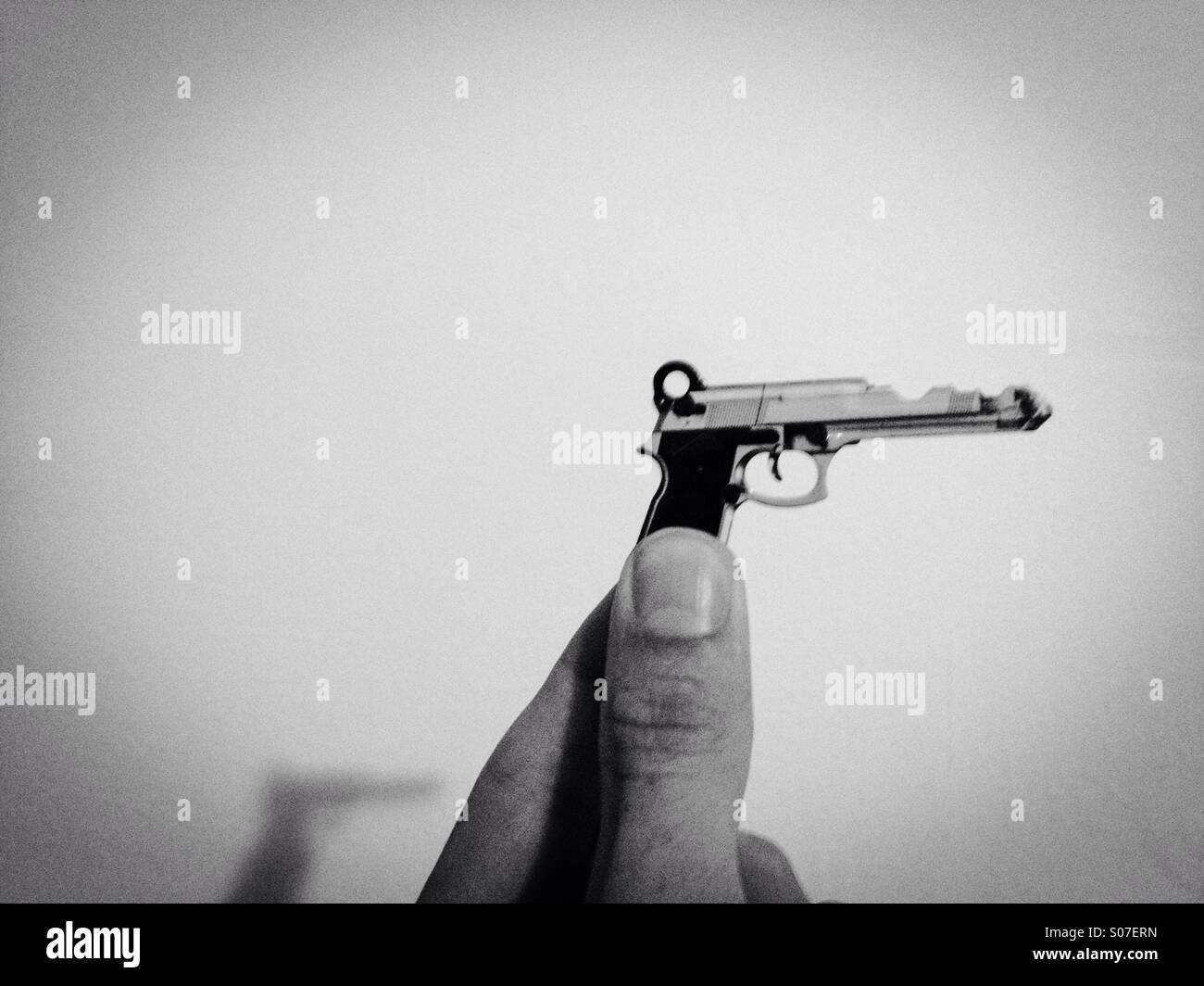 A house key in the shape of a gun - Stock Image