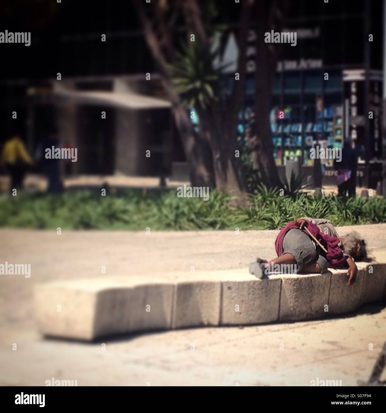 A homeless sleeps in a bench in Reforma Avenue, Mexico City, Mexico - Stock Image