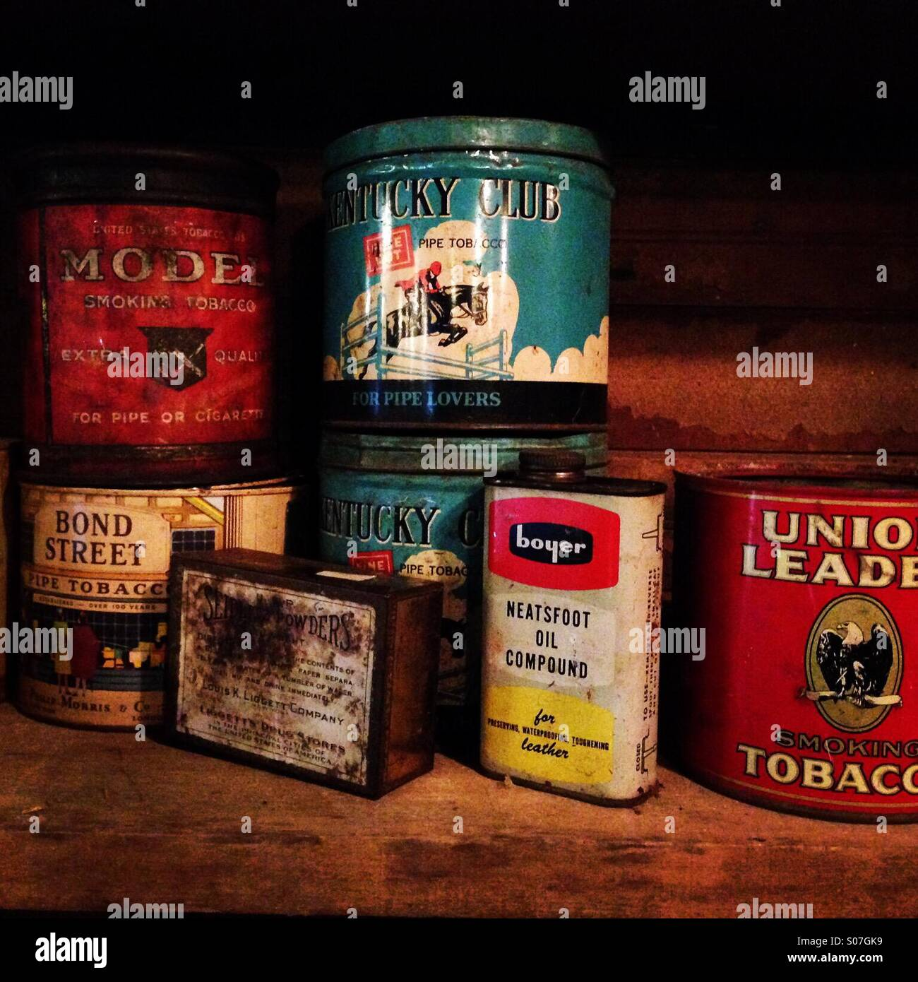 Several old tobacco tins and other items on a shelf in a long closed General Store in Tennessee. Stock Photo