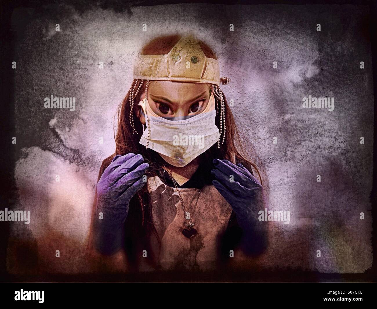 A seven-year-old girl playing dress-up with a surgical mask, gloves and crown with demonic eyes. - Stock Image