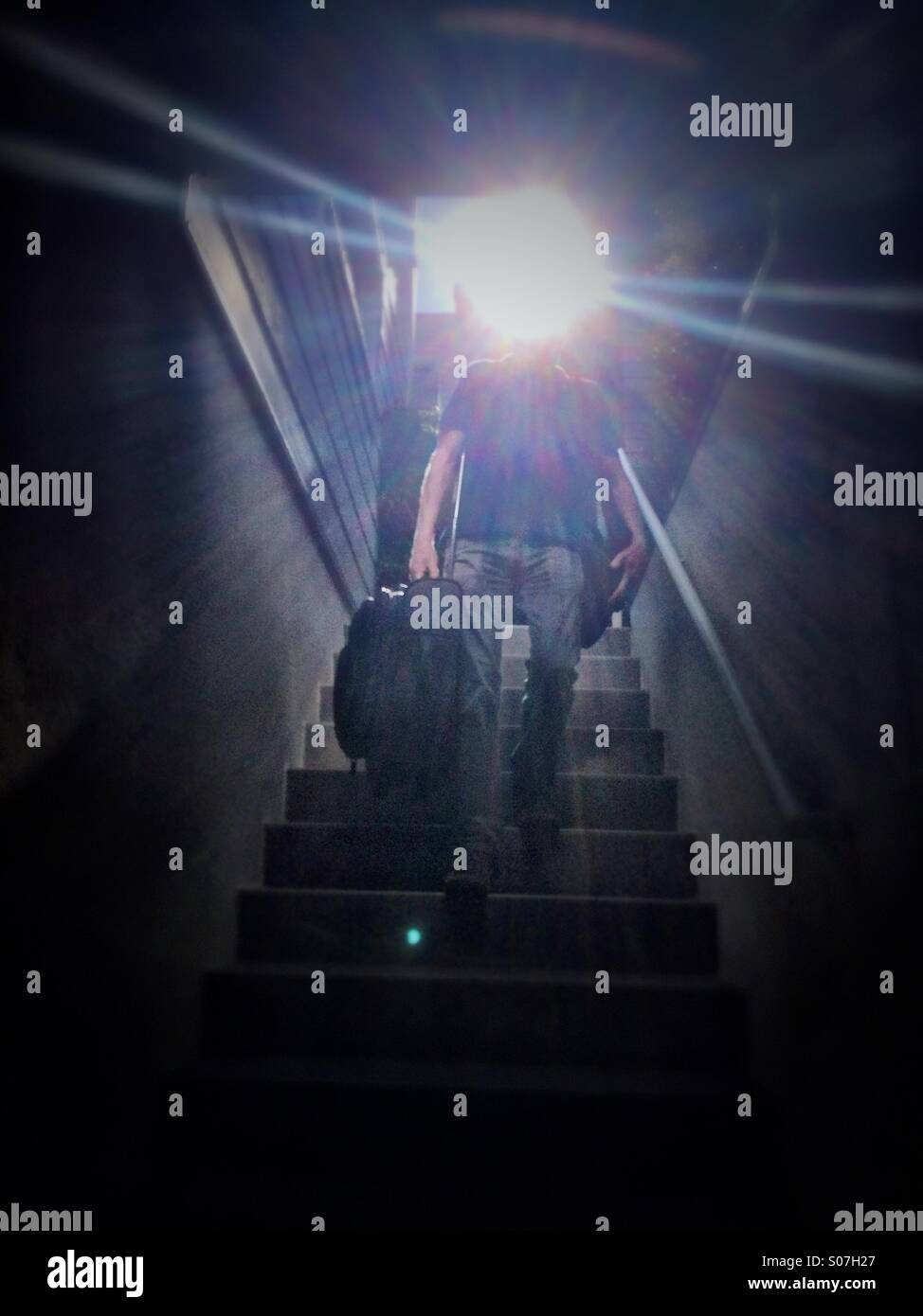 Man with suitcase walking down stairs - Stock Image