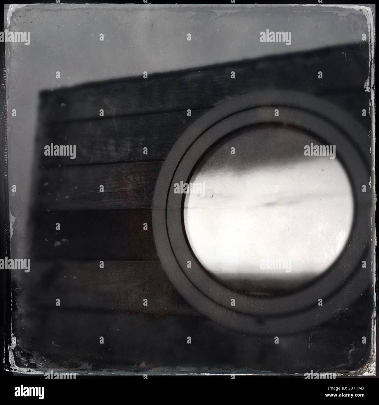 Round ship's window reflecting evening sunlight - Stock Image