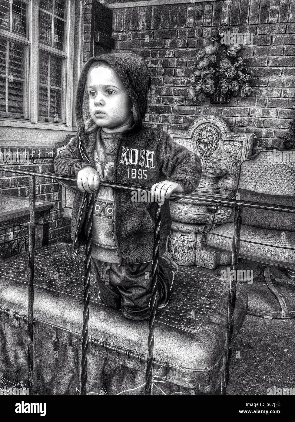 4 year old boy leaning on a porch railing and apparently thinking seriously. HDR Black & White Stock Photo
