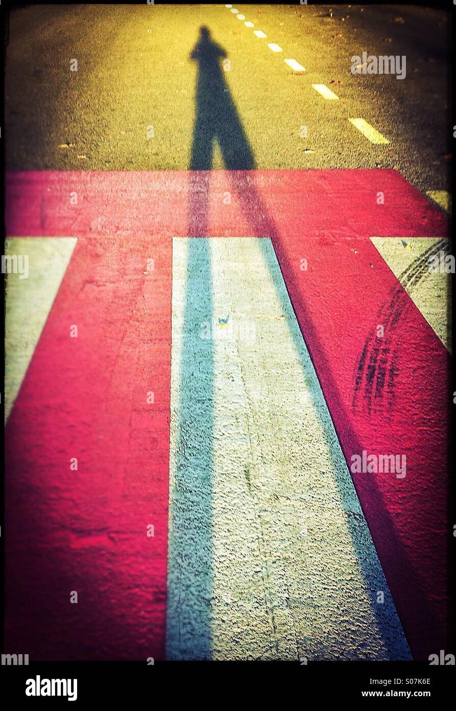Shadow of an anonymous person on a pedestrian crossing Stock Photo