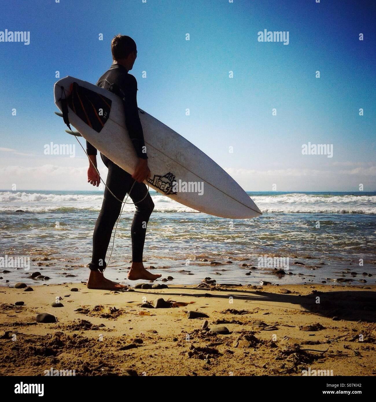 A surfer walks up the beach. Ventura California USA. Stock Photo