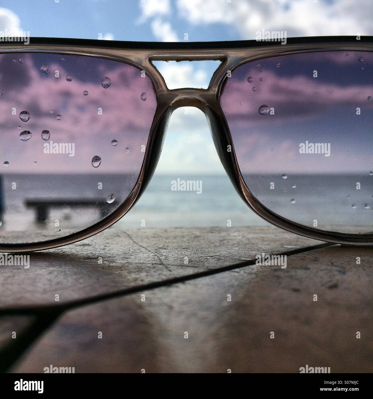 The sea thru rain soaked sunglasses - Stock Image