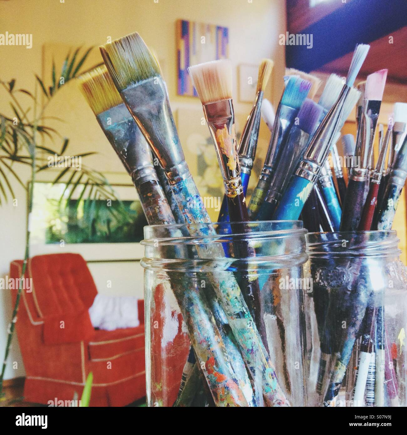 Close up of artist's paintbrushes in jars with artsy bohemian vintage background. - Stock Image
