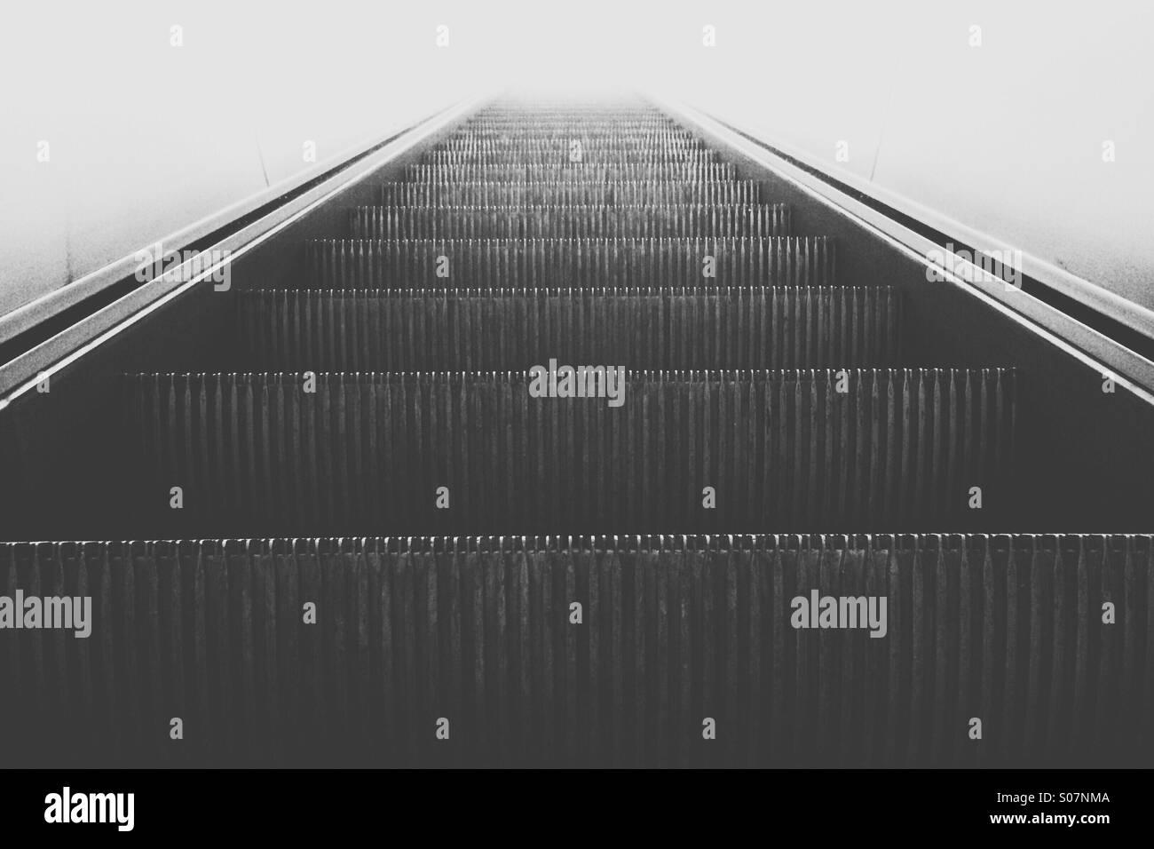 escalators moving upwards into light - Stock Image