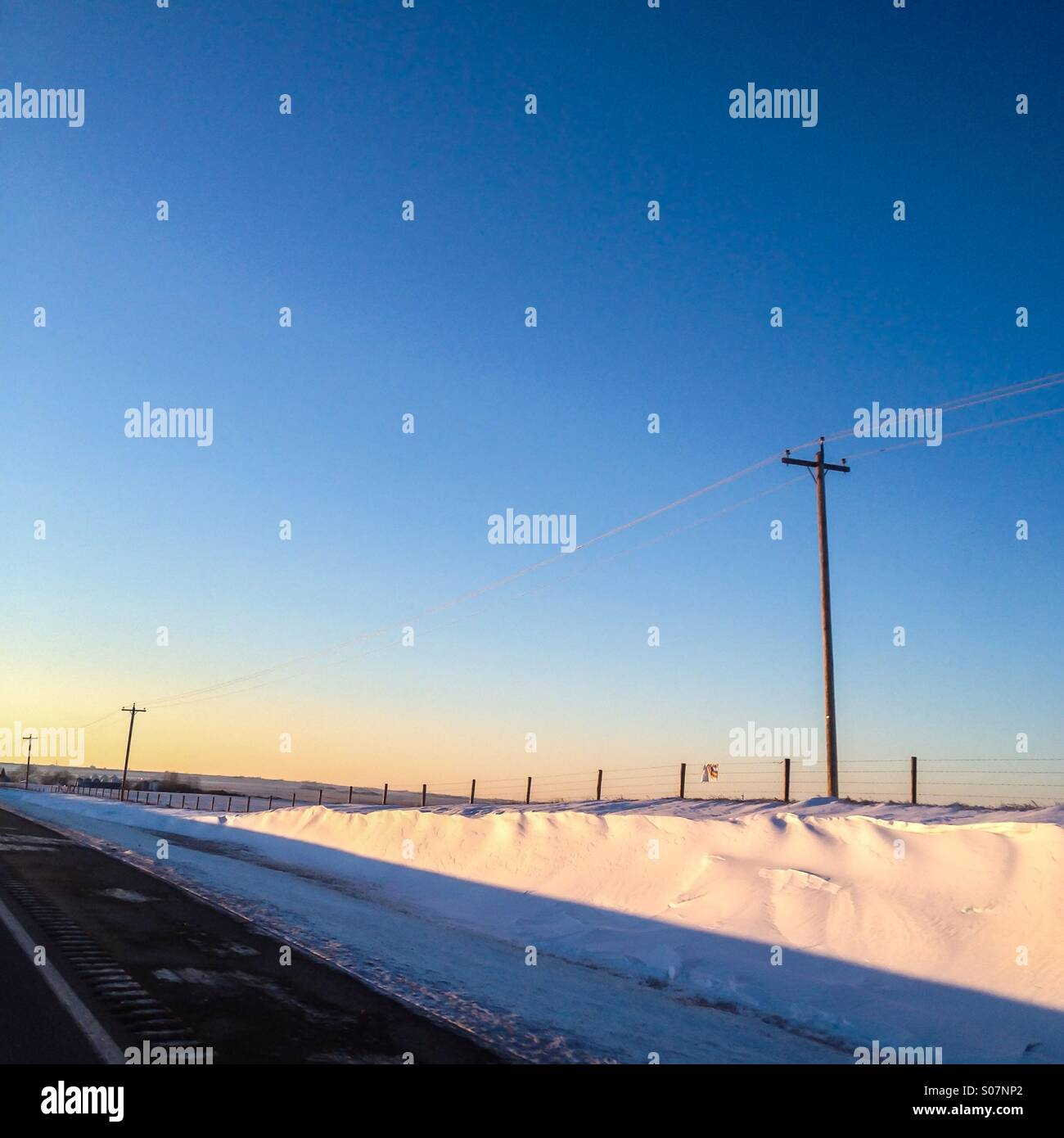Snowdrifts lit up by the setting sun along the freeway in the prairies. - Stock Image