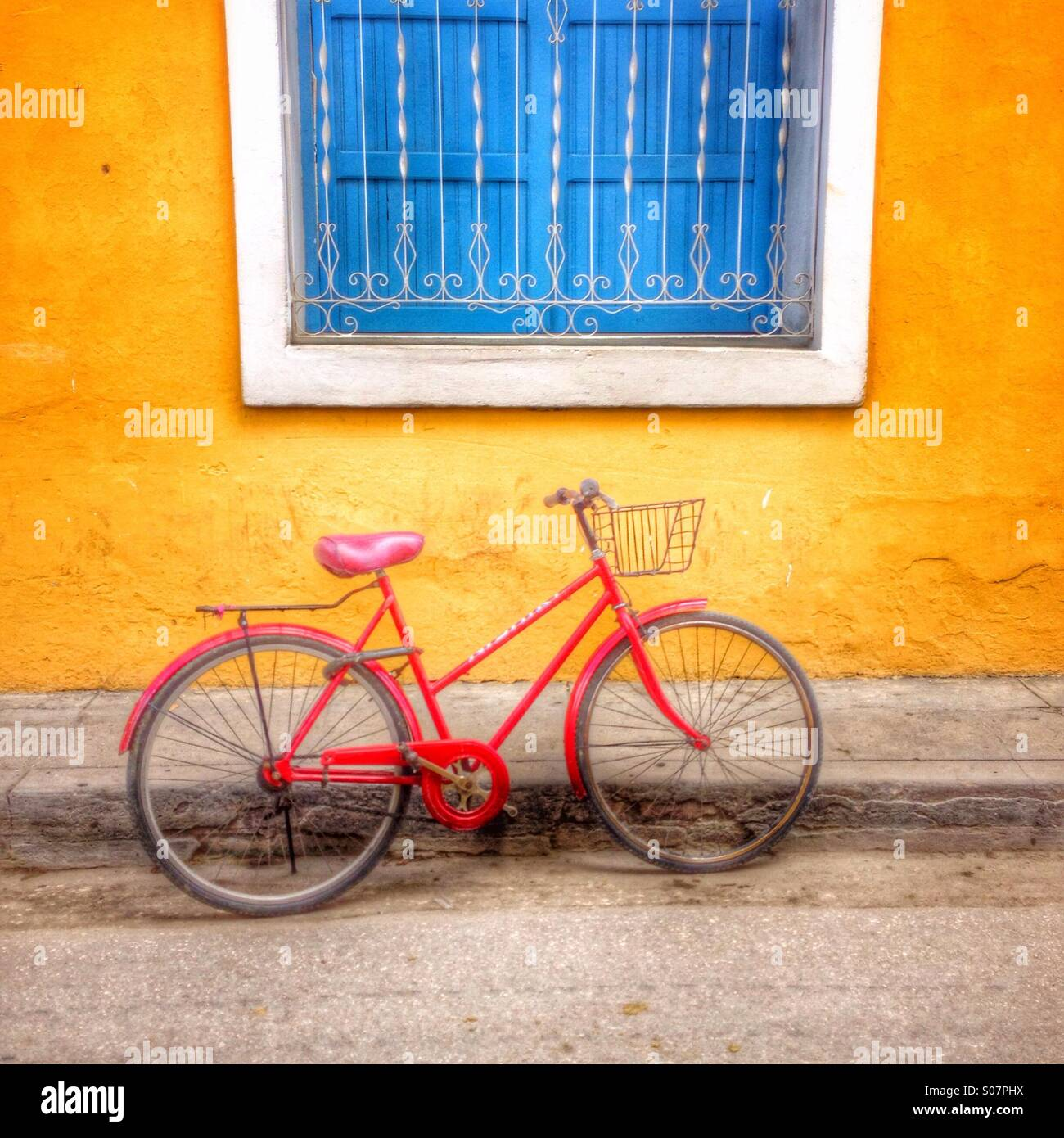 Pictorial image of red painted bicycle set against yellow painted wall with blue painted shuttered window. Trinidad - Stock Image