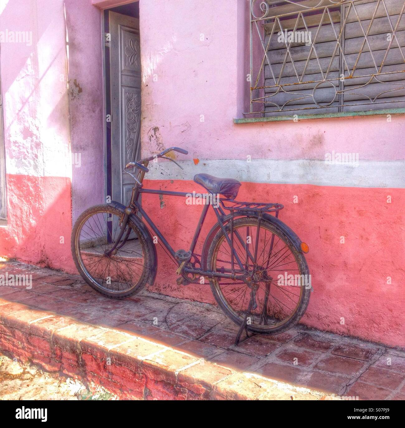 bicycles against a pink painted wall, Cuba. - Stock Image
