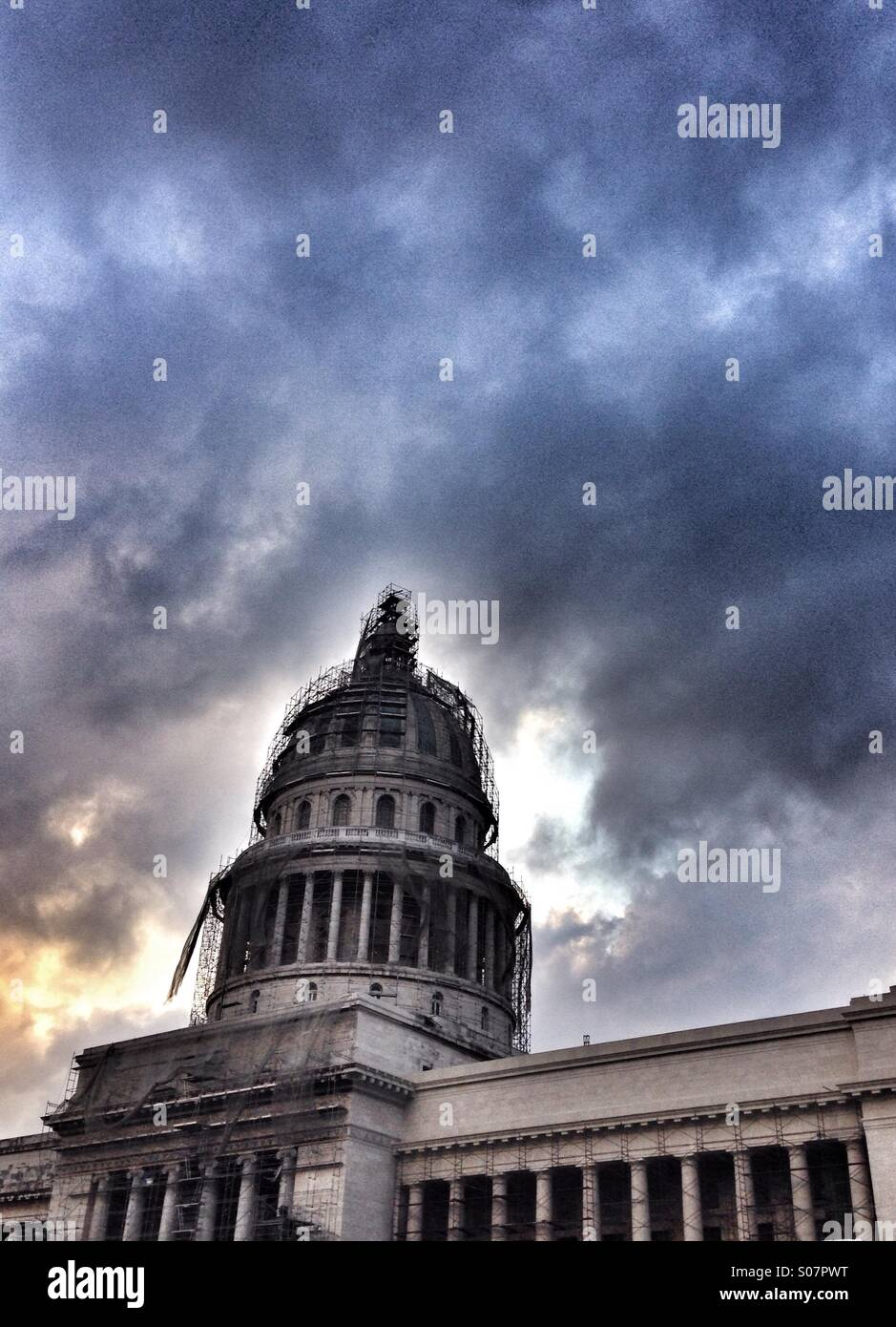 Capitol building under scaffolding, Havana, Cuba. Low angle dramatic brooding sky background. - Stock Image