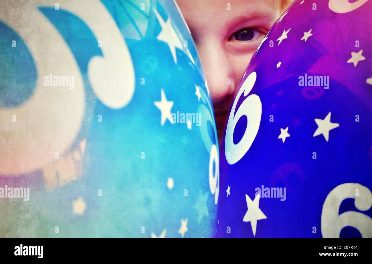 Young girl peering out from behind party balloons - Stock Image
