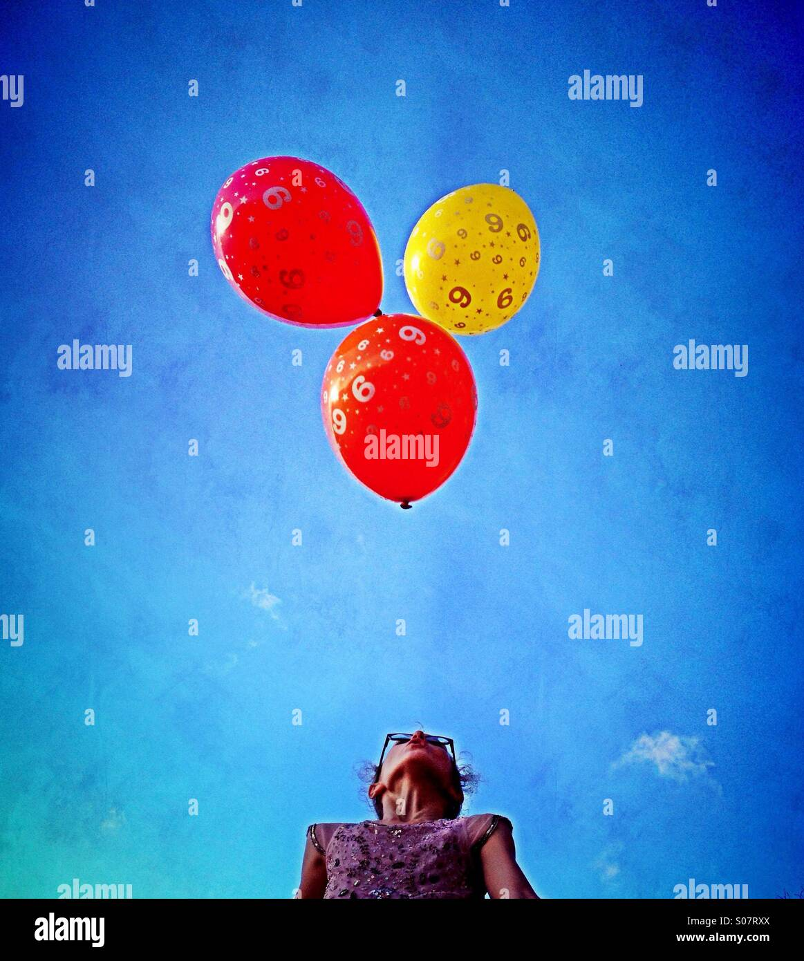 Girl blowing to keep three balloons up in air - Stock Image