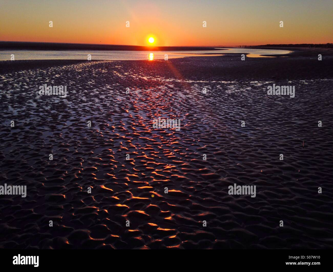 Sunset light shines on a sandbar at Kiawah Island, SC. - Stock Image