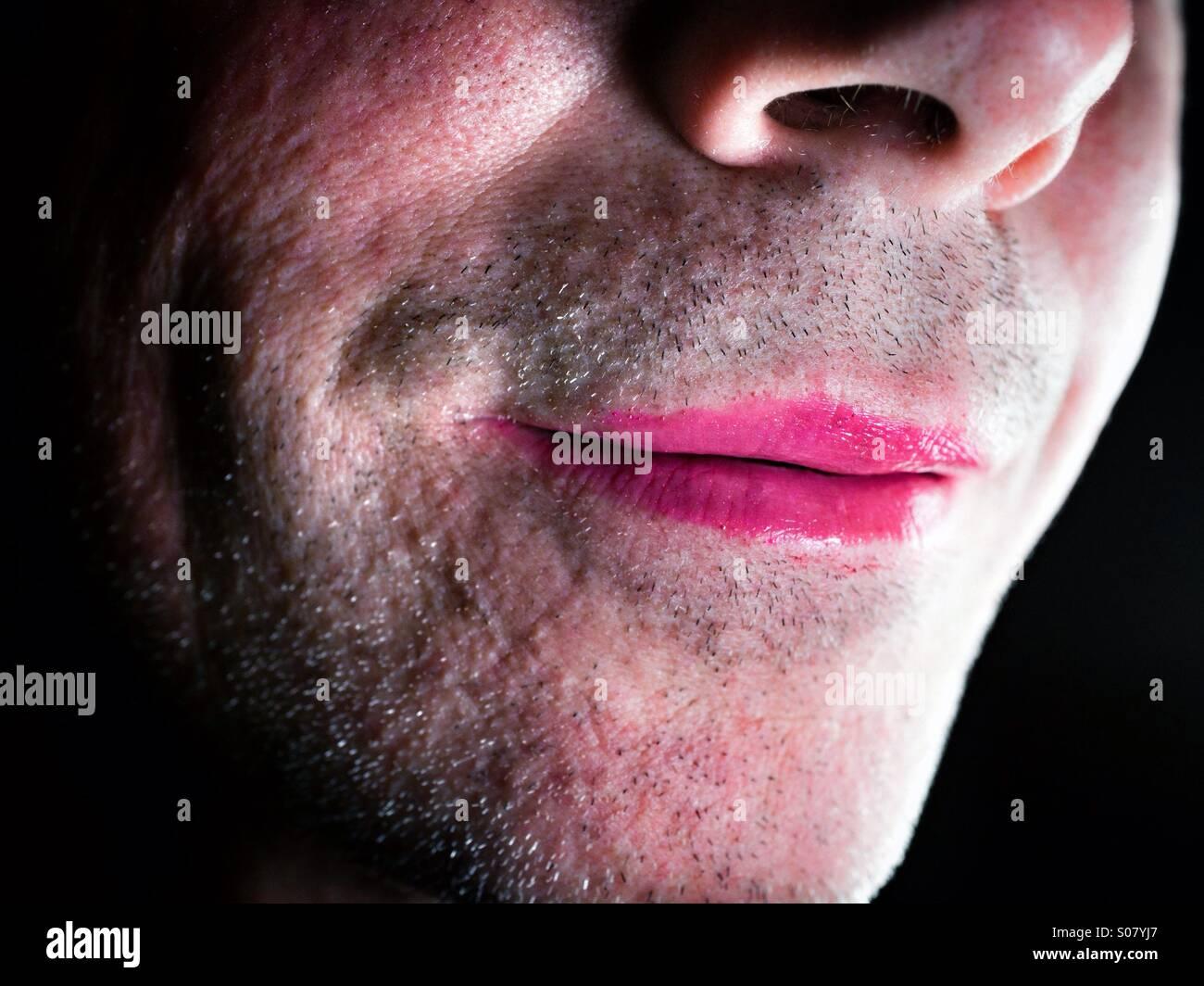Unshaven man wearing pink lipstick - Stock Image