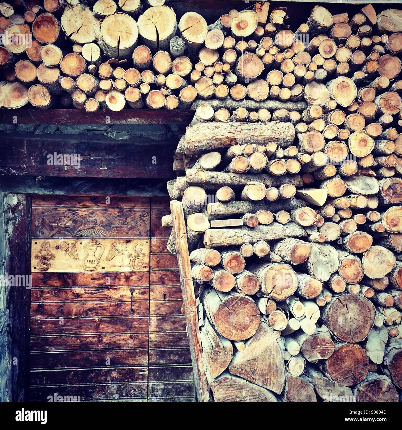 Log pile surrounding door in Grimentz, Switzerland Stock Photo
