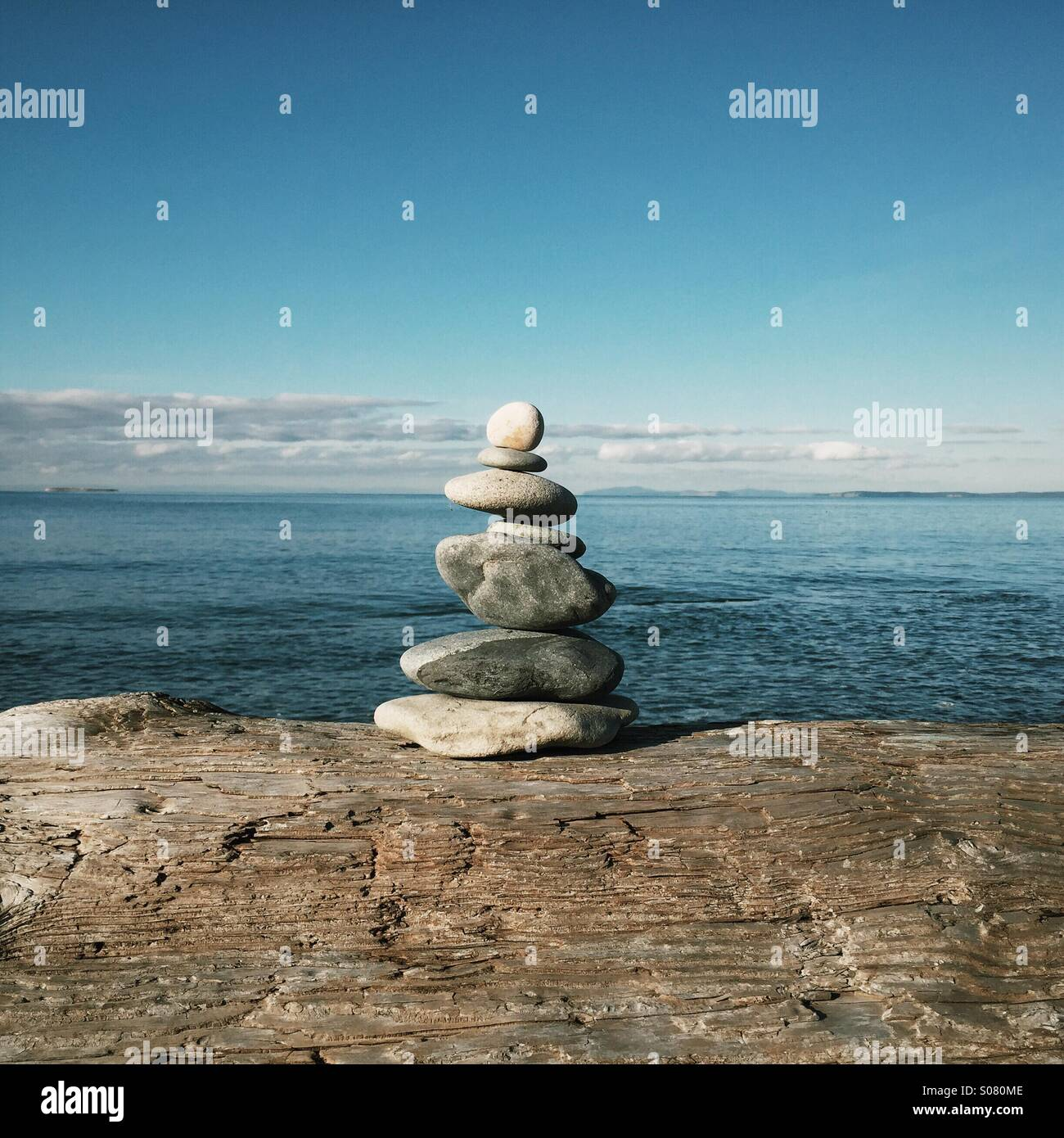 Cairn of stacked or balanced stones sitting on driftwood at the beach. - Stock Image
