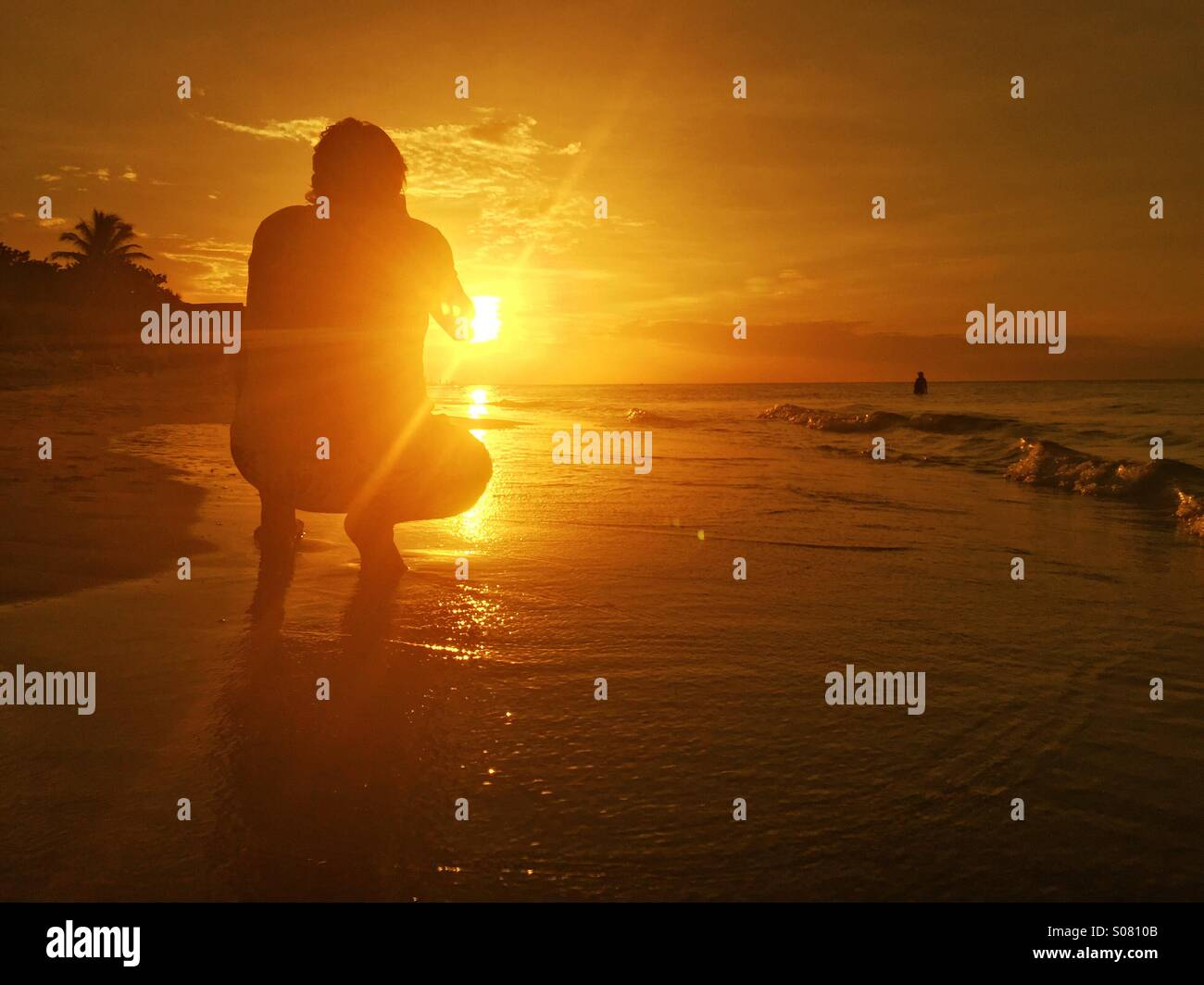 Taking a picture at sunset on the beach - Stock Image