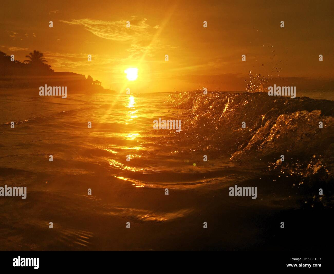 Waves at sunset on the beach - Stock Image