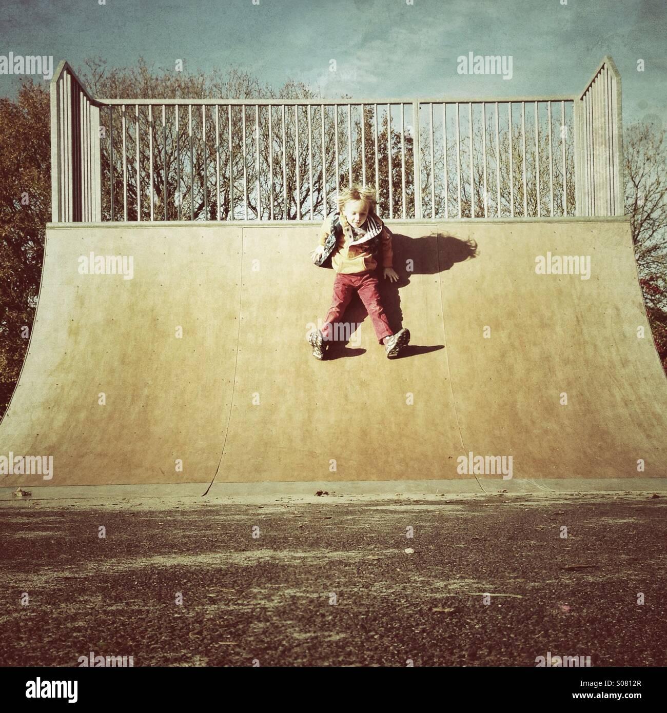 Sliding down a skate ramp - Stock Image