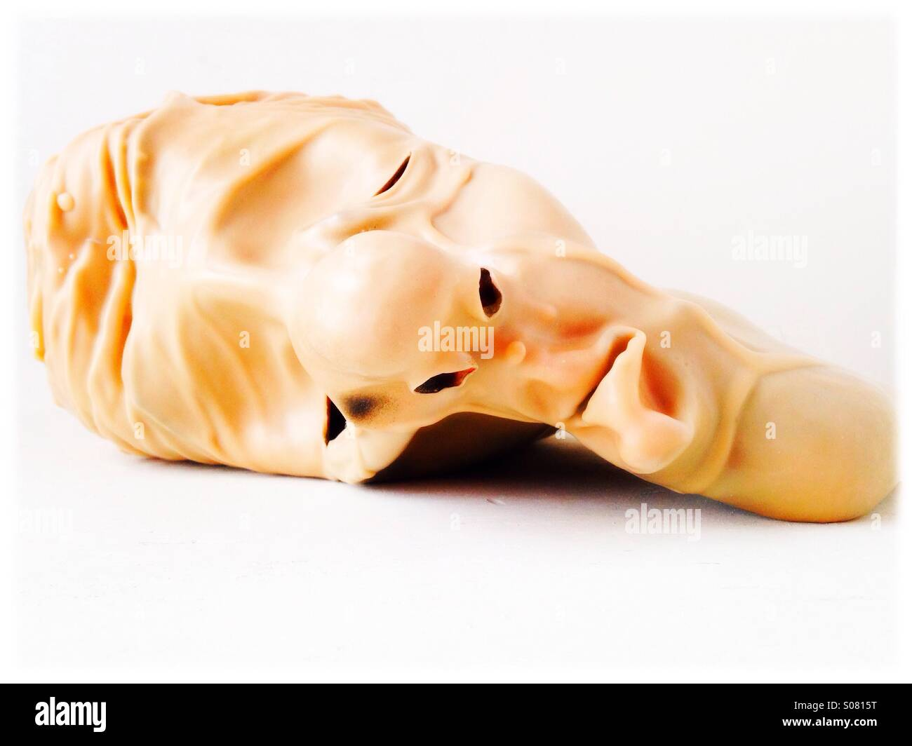 A deflated rubber mask of a man's face. - Stock Image