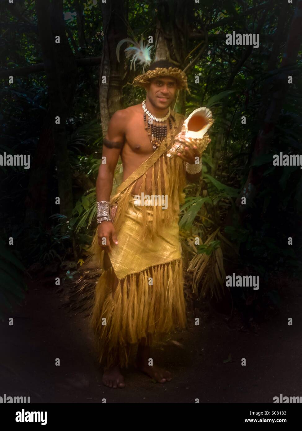 Native warrior in Vanuatu in traditional dress holding a Conch shell - Stock Image