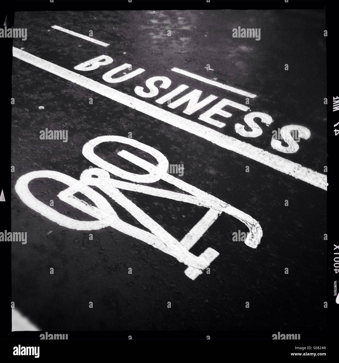 Painted signs on road: business and cycle - Stock Image