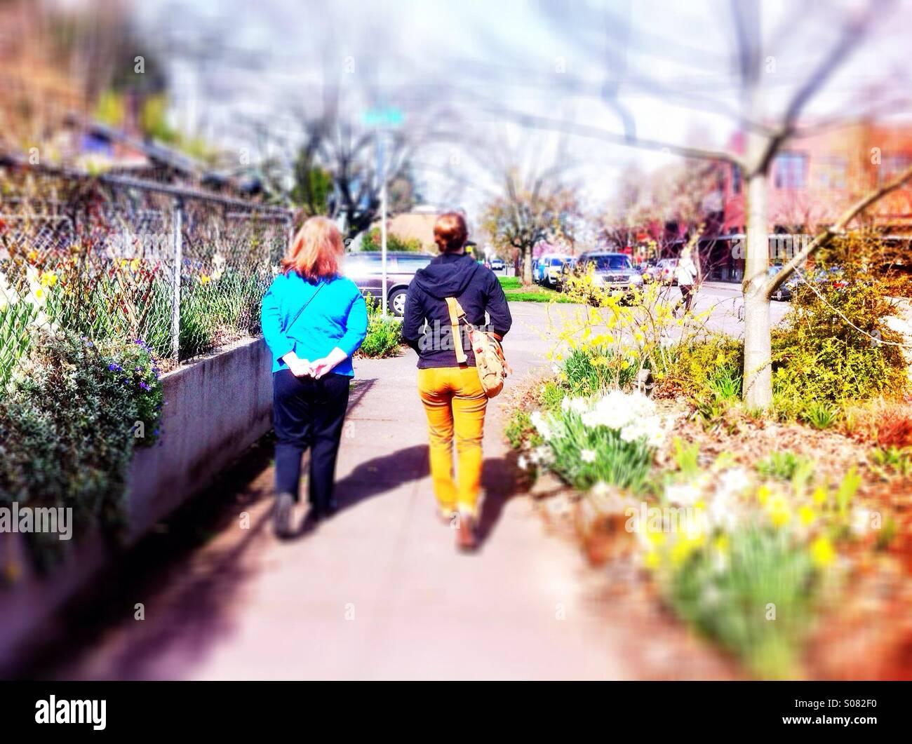 Two women walking on sidewalk in spring - Stock Image