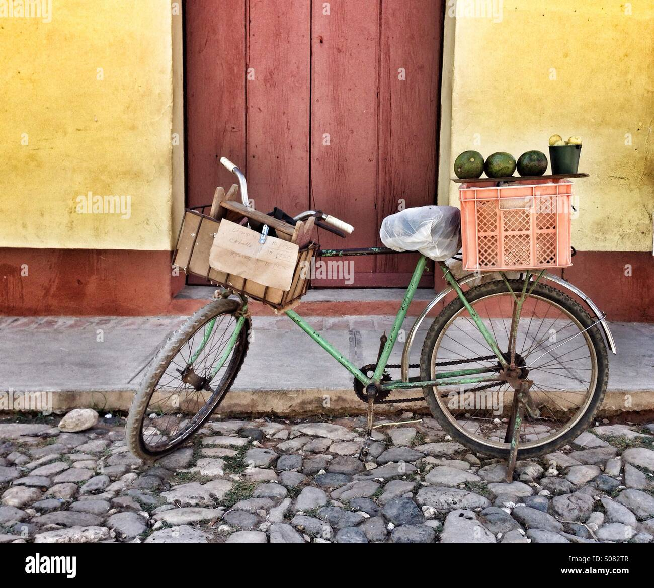 Fruit seller's bicycle with fruit produce lined up on a box at rear of bike. Stood in cobbled street in front - Stock Image