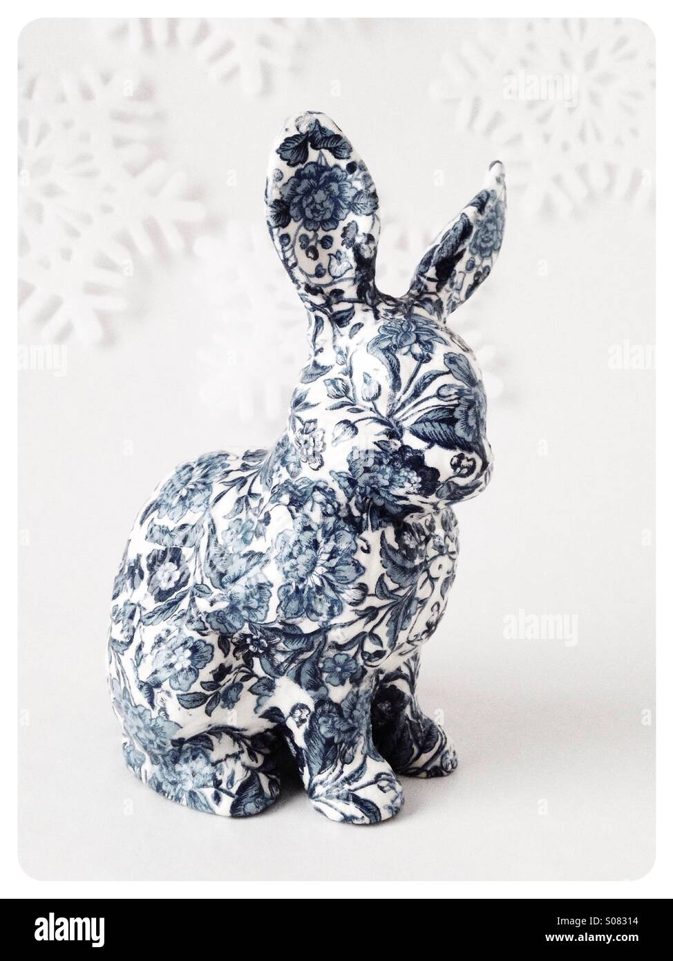 A bunny figurine with a snowflake background. - Stock Image