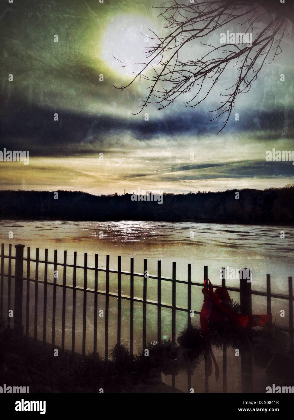 A fence with garland and a red bow while the sun shines on the Ohio River. - Stock Image