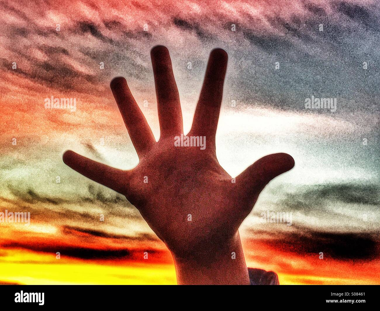 Child's hand against sunset - Stock Image