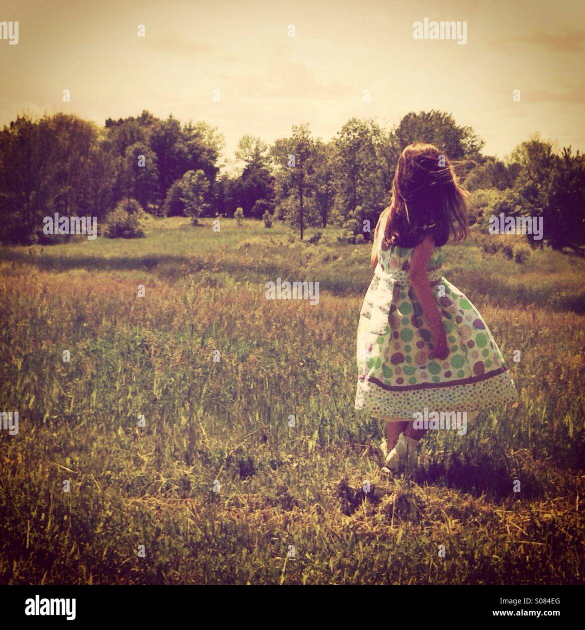 A little girl walks in a field, she turns toward the forest in the distance lending a sense of mystery to the image. - Stock Image