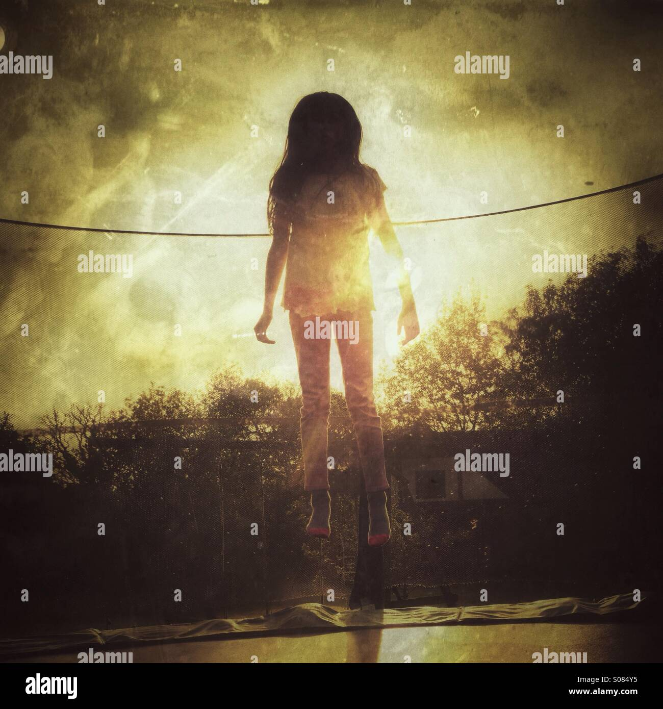 Angel - Young girl bouncing on trampoline - Stock Image