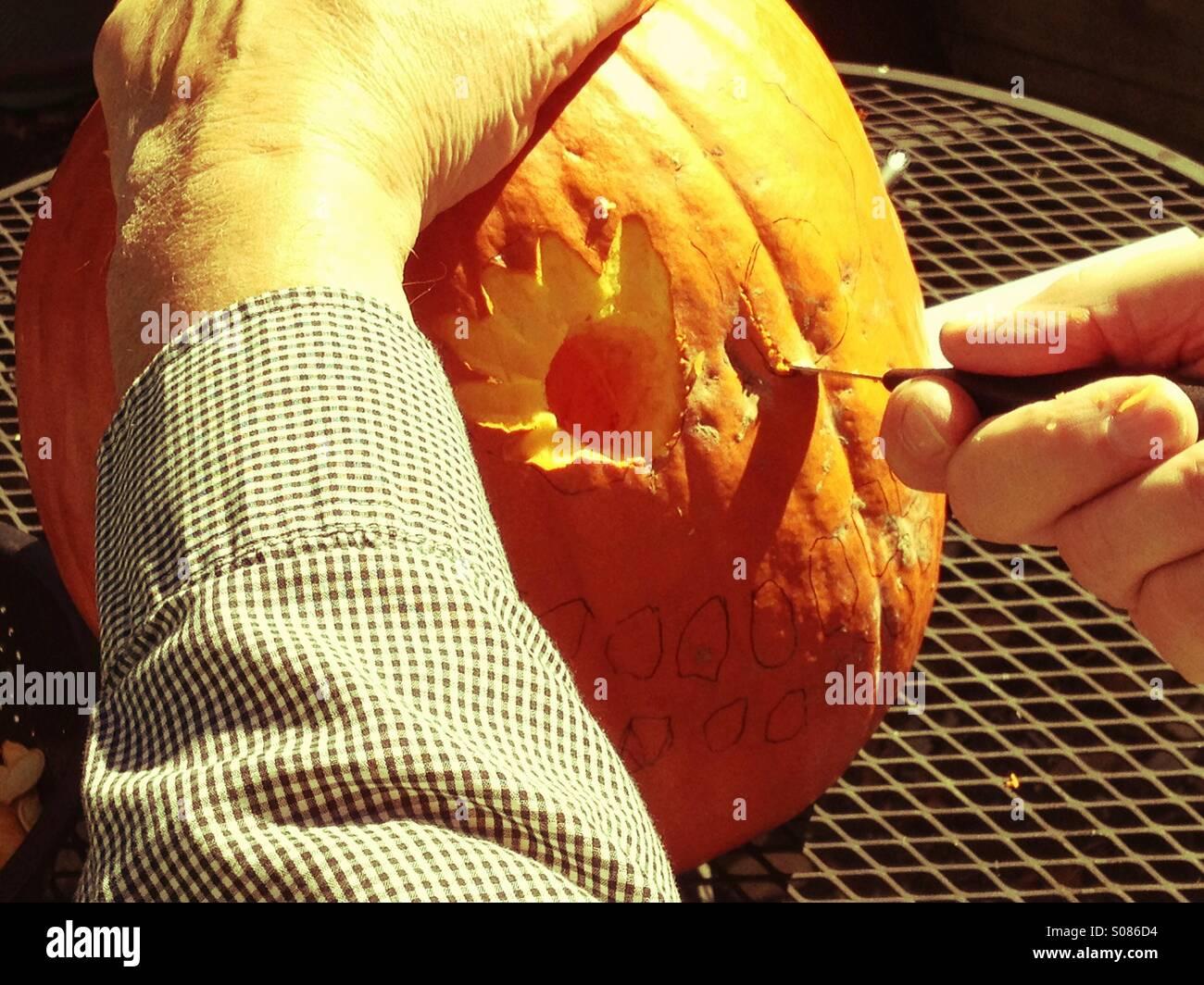 Man carves pumpkin at Halloween - Stock Image