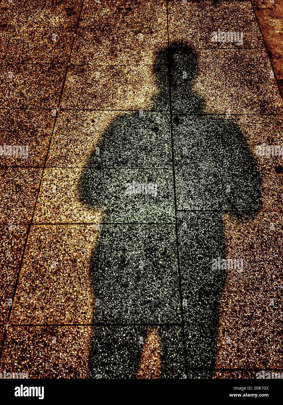 Shadow of a man on the pavement - Stock Image