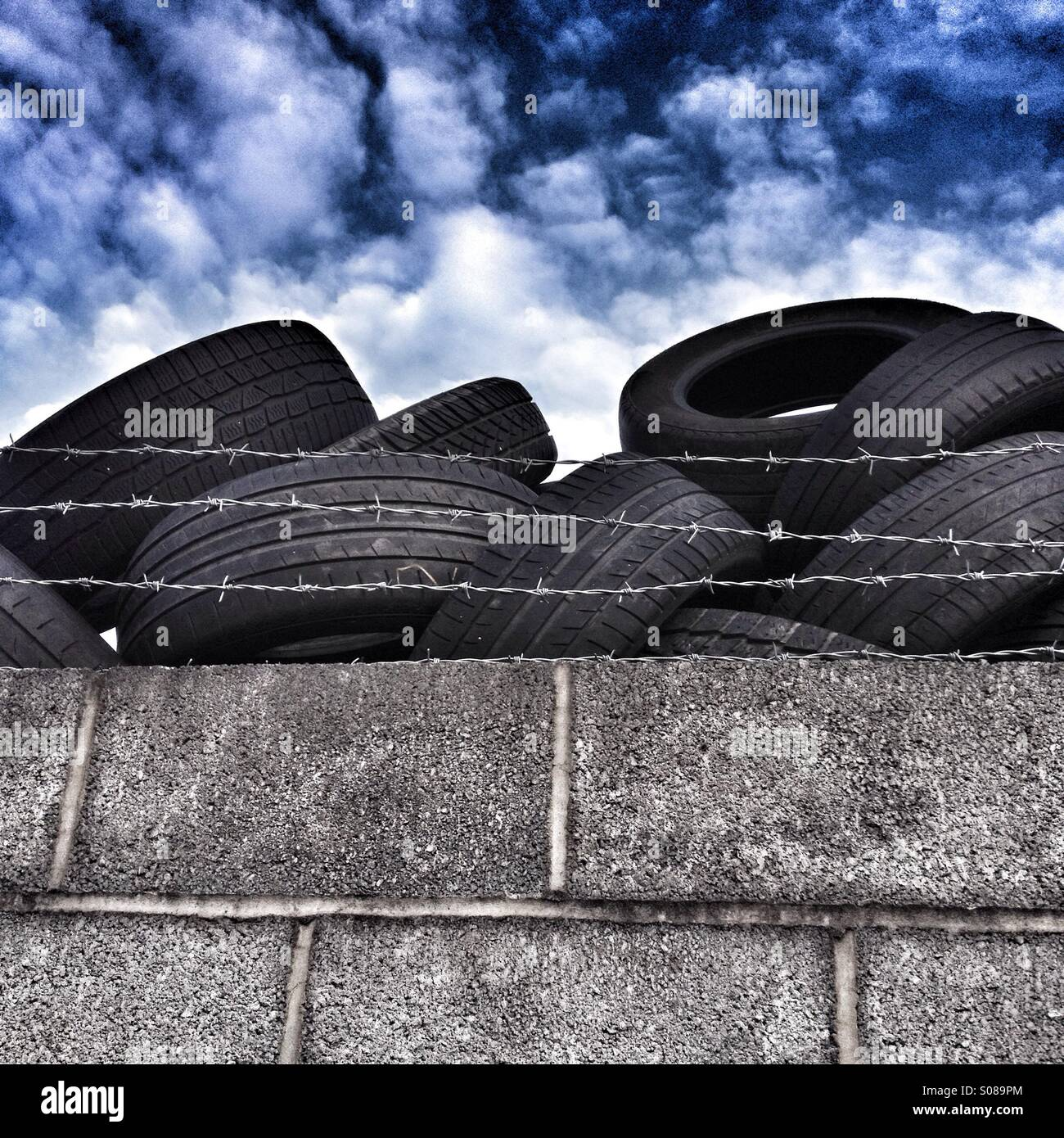 Old motor vehicle tyres behind a wall and barbed wire under a dramatic sky - Stock Image