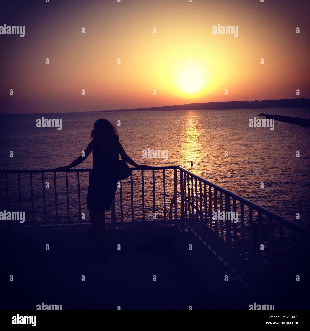 Woman looking at sunset - Stock Image