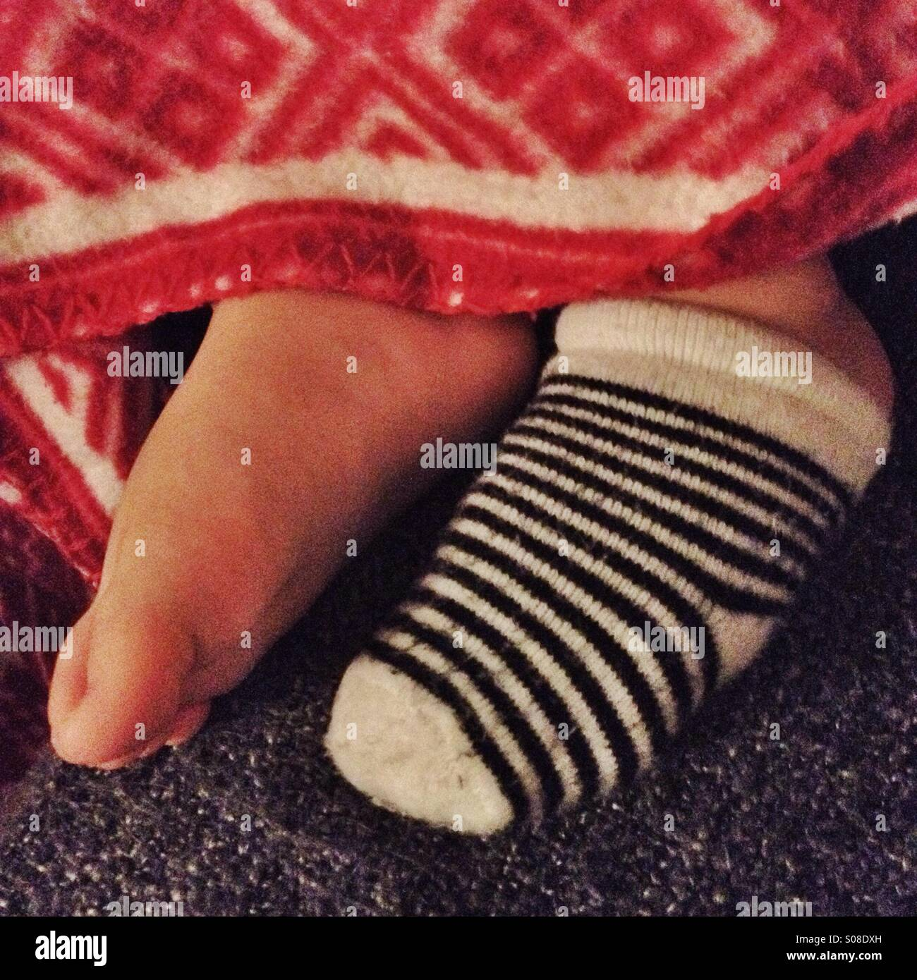 Child's feet sticking out of red blanket with one stripy sock on one foot and the other foot bare. - Stock Image