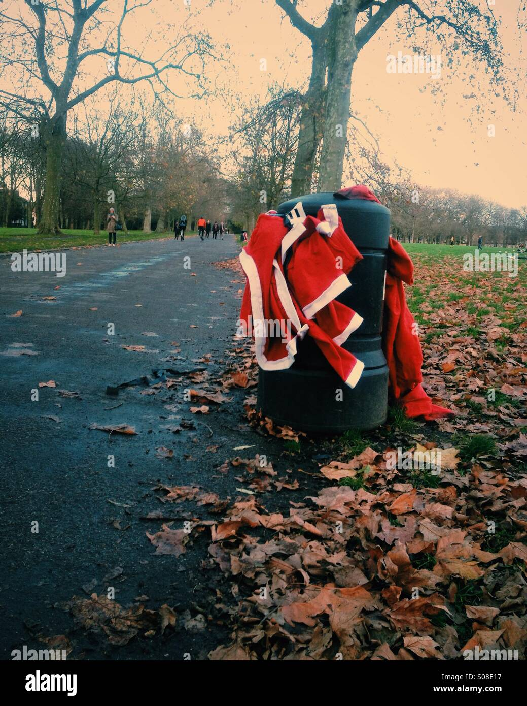 Santa costumes in a trash can after a Santa Run Charity event, London. - Stock Image