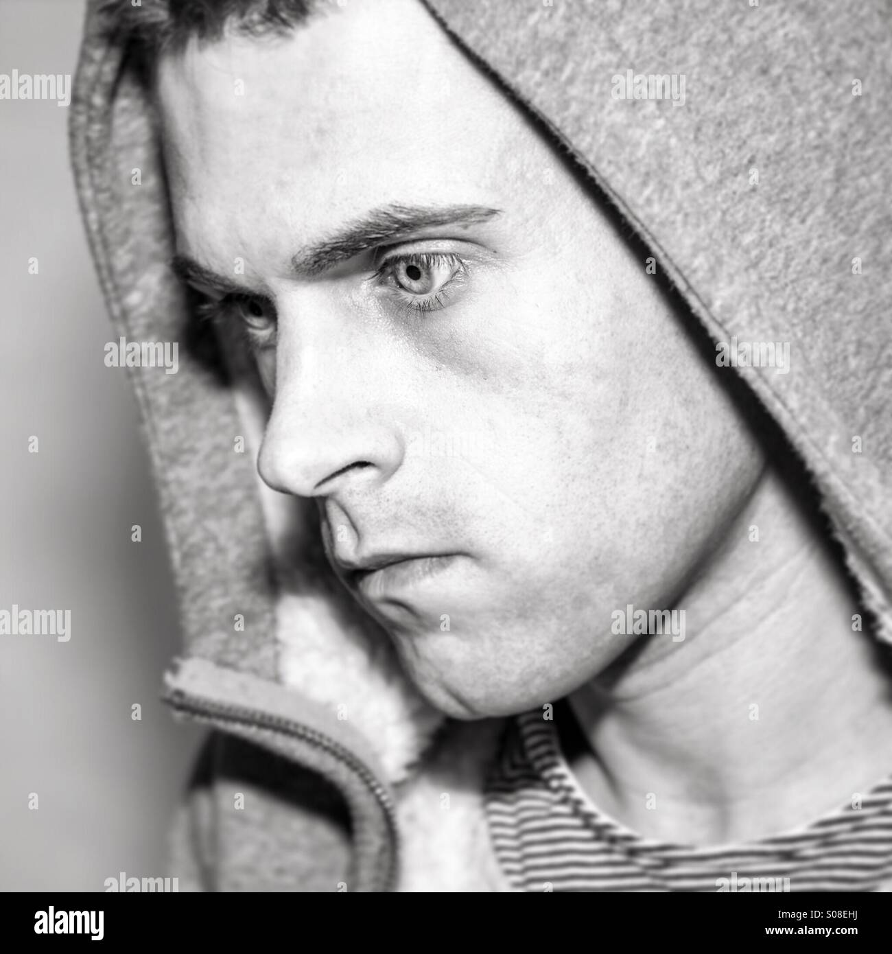 Young male staring away from camera wearing hood - Stock Image