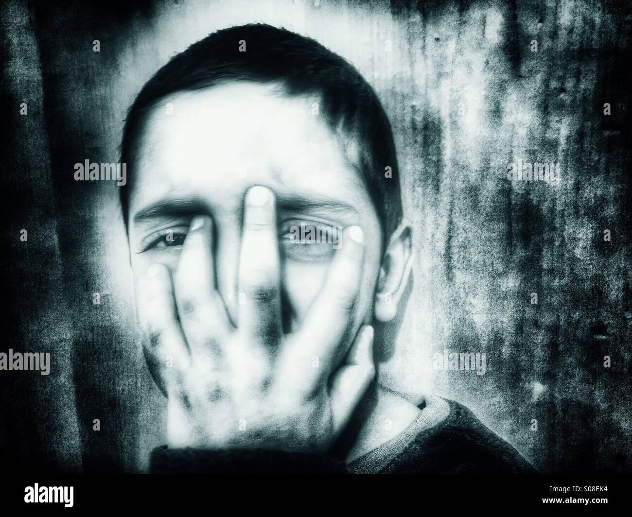 Scared boy hiding face - Stock Image